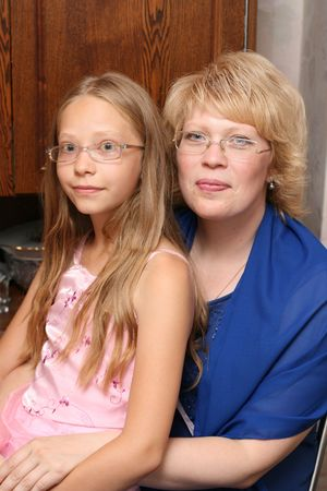 the case before: Portrait of mother and the daughter sitting on a chair before a case