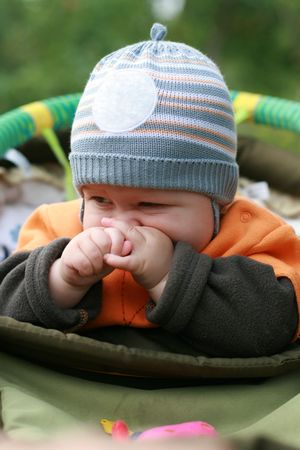 lamentation: The child in a carriage in the street, a nose rubbing by hands Stock Photo