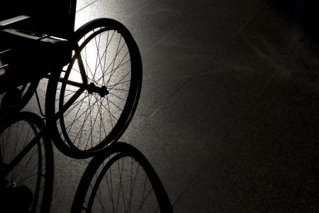 enfants handicap�s: Gros plan en fauteuil roulant vide sur fond sombre et l'ombre