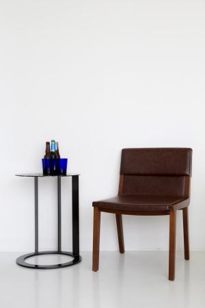 Stuhl: Wei�e Wand-und Leder-Sessel mit Trinkwasser auf dem Tisch