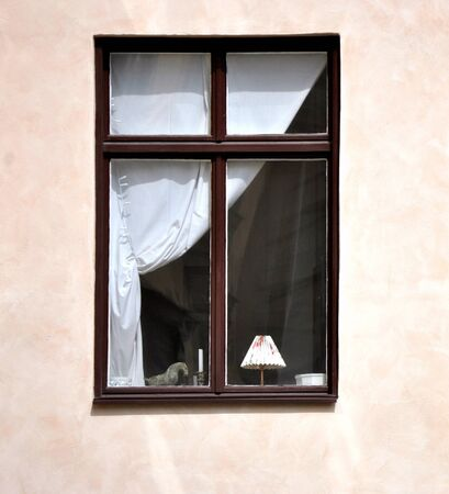 window shade: The window in the house, brown frame with a white curtain.