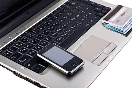 mobile phone with credit cards on laptop Sajtókép