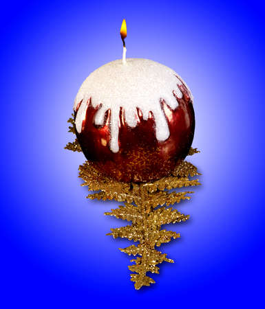 decorative candle burning on a branch. Blue background. photo