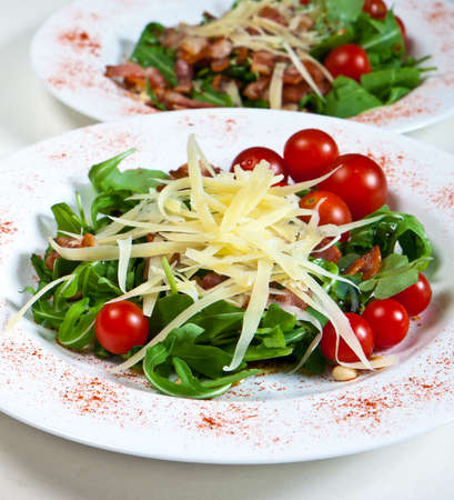 Arugula with tomatoes cheese bacon and pine nuts Stock Photo - 11030186