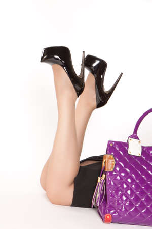 Woman in black high heels lying on the floor near purple bag photo