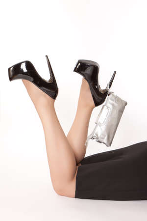Woman is lying on the floor and keeping silver clutch on the heel photo