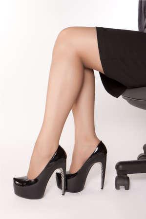 Üzletasszonyok magas sarkú cipő viselése fekete cipő, és ült a széken