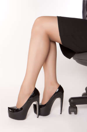 Businesswomen wearing high heels black shoes and sitting on the chair