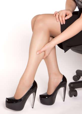 piernas con tacones: Las mujeres que usan tacones altos zapatos negros, sentado en la silla y el masaje de las piernas cansadas