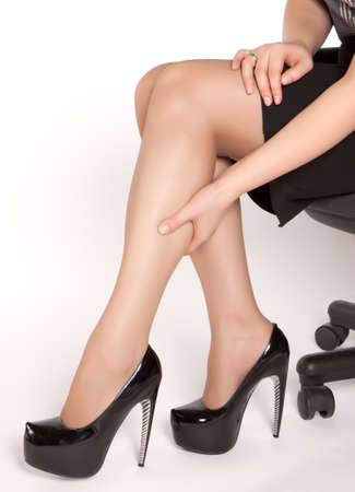 Women wearing high heels black shoes, sitting on the chair and massaging tired legs photo