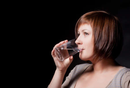 young woman with glass water, black background photo