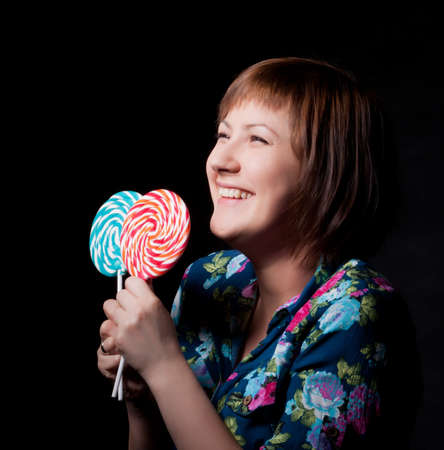 young woman with lollipop, black background photo