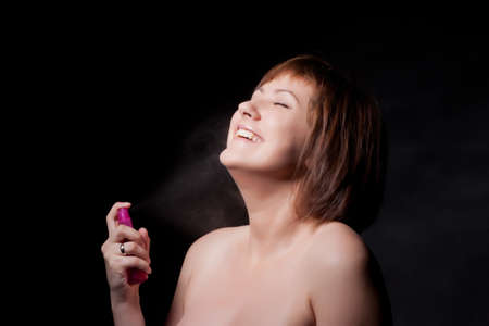 young woman with spray, black background photo