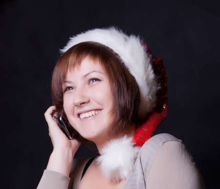 young woman in christmas cap, black background photo
