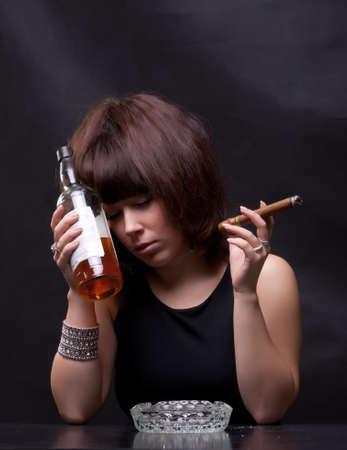 ubriaco: foto di donna beve alcol e fuma un sigaro