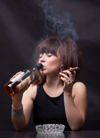 chica fumando: foto de una mujer bebe alcohol y fuma un cigarro
