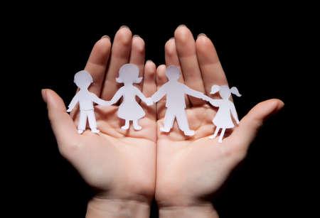 Papír lánc családi védett tenyeréből a fekete háttér