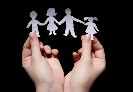 Paper chain family in hands on black background photo