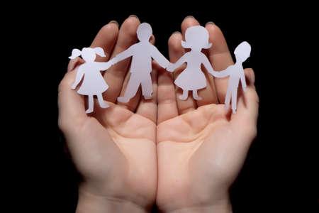proteccion: Papel de la familia de la cadena protegidos en las manos ahuecadas sobre fondo negro