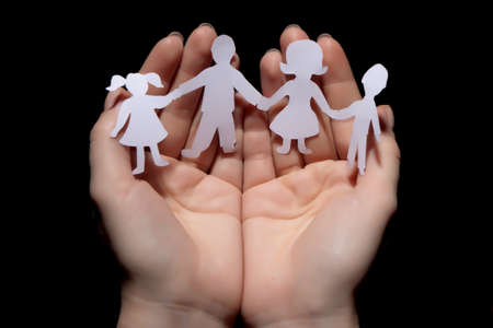 protect family: Paper chain family protected in cupped hands on black background