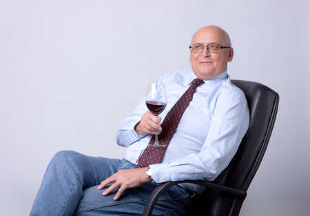 portrait of a successful senior man with glass of wine on gray background photo