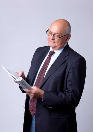 portrait of a successful senior man with book on gray background photo