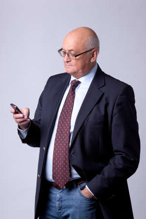 portrait of a successful senior man with phone on gray background photo