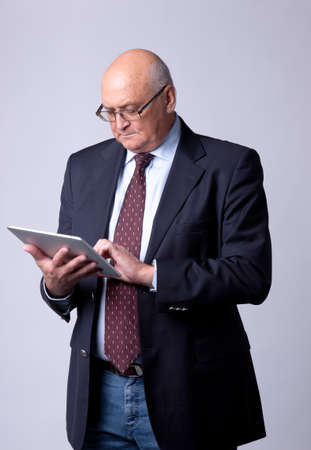 portrait of a successful senior man with tablet on gray background photo