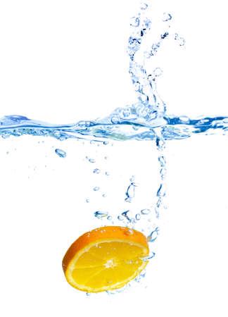 dropped: De naranja fresco ha ca�do al agua con splash aislado en blanco
