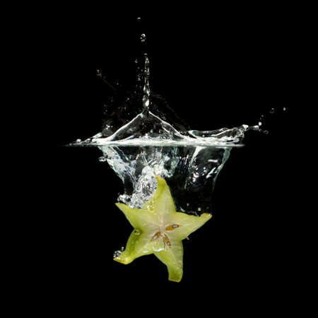 carambola splashing in water over black background photo