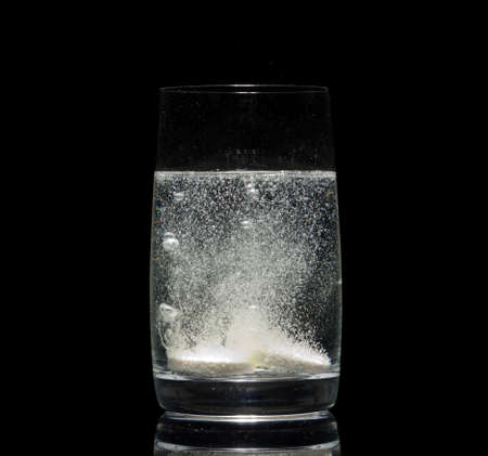 aspirin tablet in glass of water over black Stock Photo - 12229120
