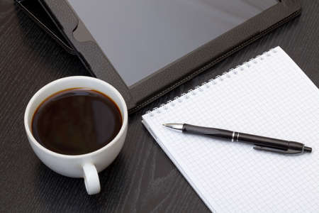 Coffee cup, tablet, spiral notebook and pen on the wooden table photo