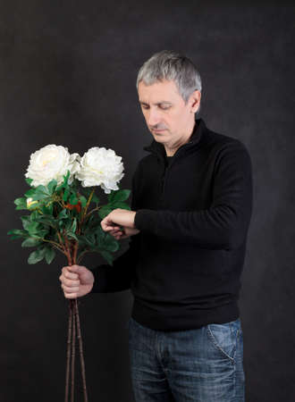 suitor: Man holding a bouquet of flowers on gray background Stock Photo