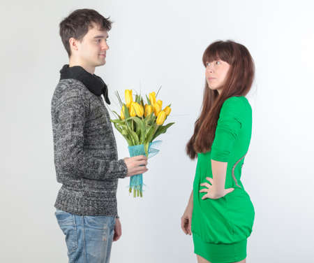 happy young couple with bouquet flowers, on gray background