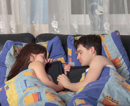 Young couple asleep in an embrace with a tablet laptop Stock Photo - 12673384