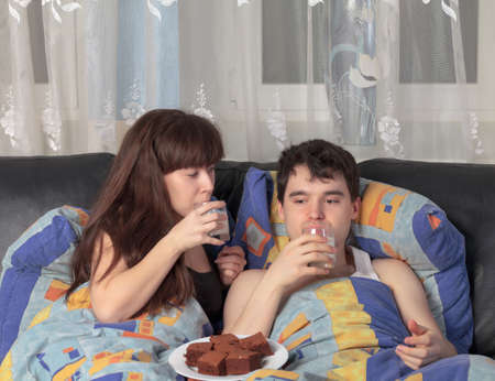 A young couple has breakfast in bed Stock Photo - 12673477