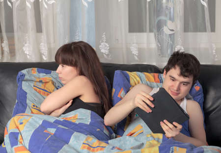 Young couple using tablet PC in their bed photo