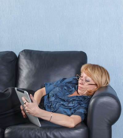 Portrait of relaxed middle aged woman using tablet PC on couch photo