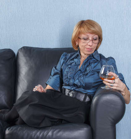 Portrait of relaxed middle aged woman with a glass brandy on couch photo