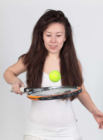 Young woman with tennis racket isolated on white photo
