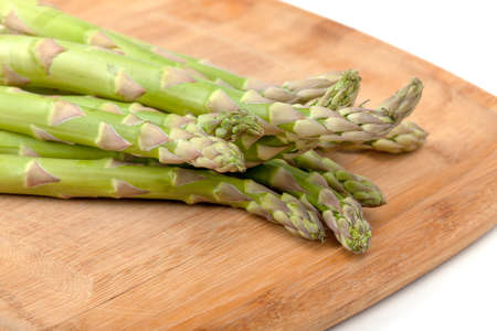Bunch of fresh asparagus on cutting board photo