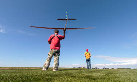 Man launches into the sky RC glider, wide-angle Stock Photo