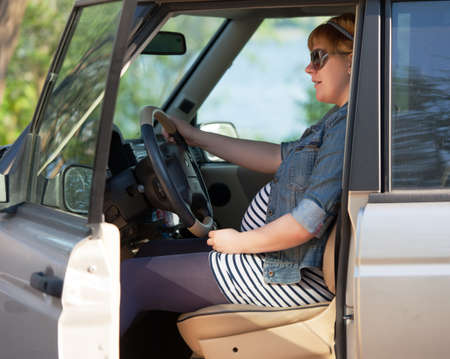 Pregnant woman at the wheel of big car photo