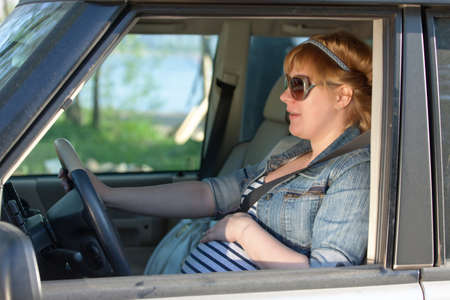 Pregnant woman speaking to her belly in the car photo