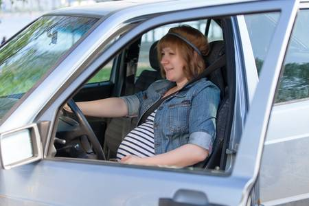 Pregnant woman in driving seat of the car photo