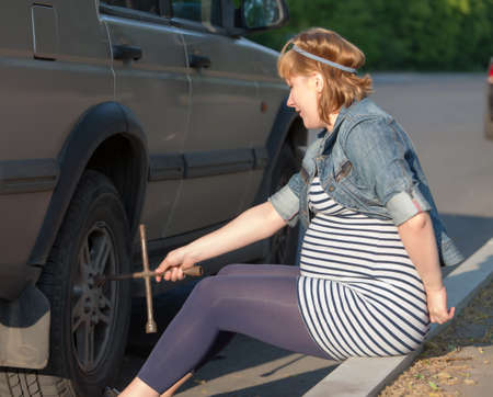 Pregnant Woman with a Wheel Brace near Car Stock Photo - 13797791