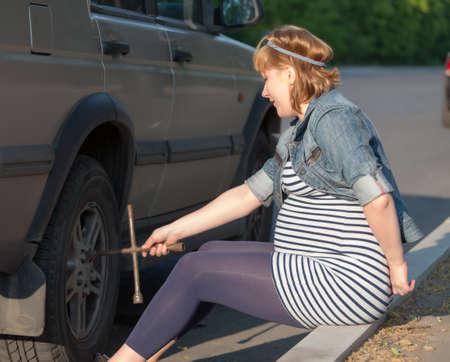 Pregnant Woman with a Wheel Brace near Car Stock Photo - 13797791