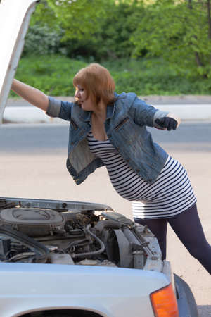 Pregnant Woman Opens the Hood of the Car Stock Photo - 13797988
