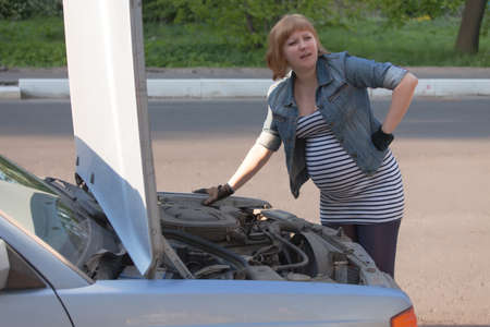 Pregnant Woman Trying to Repair the Car Stock Photo - 13797967