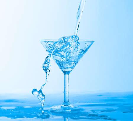 Water Splashing in a Wineglass, on blue background photo